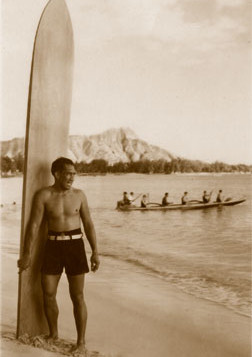 A black and white historical photo of Duke Kahanamoku standing with his surfboard in Waikiki