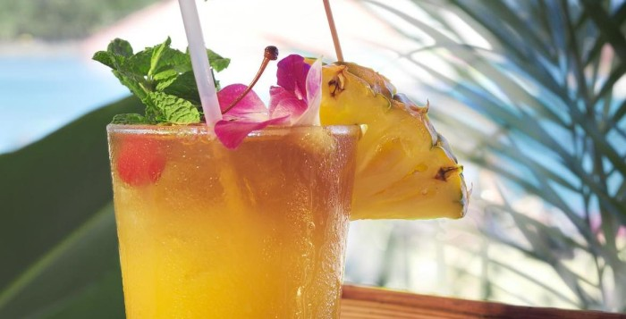 A tropical mai tai drink with a slice of pineapple and an umbrella