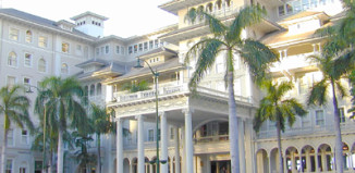 The Moana Surfrider Hotel surrounded by palm trees in Waikiki
