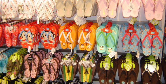 Four rows of rubber slippers shown in a local shop