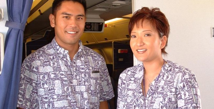 Flight attendants stand in the airplane smiling