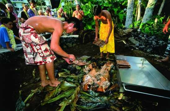 People dressed in aloha attire prepare food for a traditional Hawaiian luau