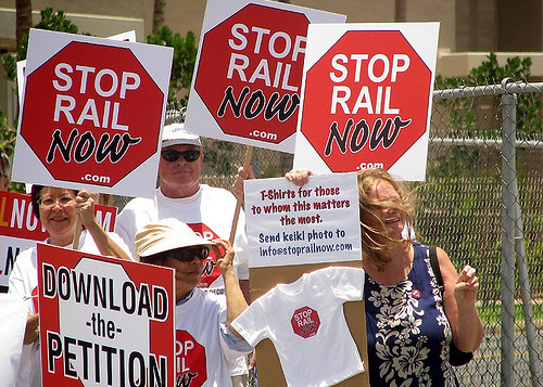 Hawaii residents rally outside with signs protesting the rail project on Oahu