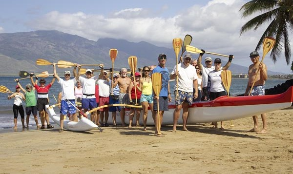 A team of canoe paddlers raise their paddles in celebration