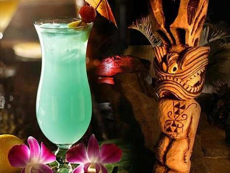 A beautiful glowing tall glass of colored liquid with an umbrella, a slice of pineapple and a tiki carving sitting next to the drink