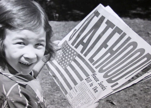 Little girl holds newspaper announcing statehood