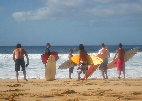 5 local hawaiian surfers standing on a beach.