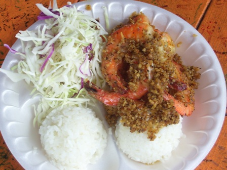 A white styrofoam plate of garlic shrimp with 2 scoops rice and salad