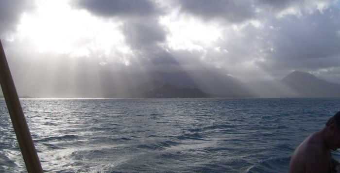 Light rays stream through holes in the dark clouds at Kaneohe Bay