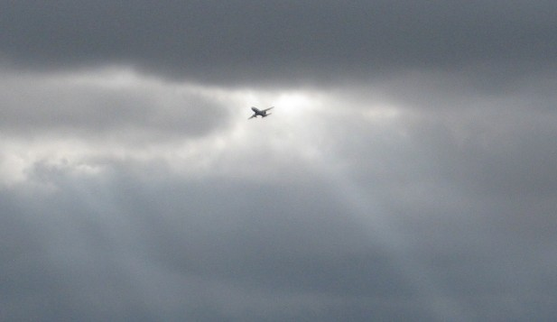 A jet airplane and some dark clouds from the ground