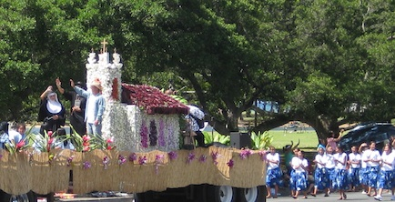 A parade float with 3 people waving