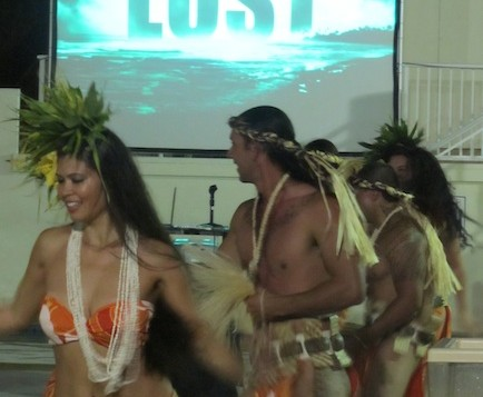 Traditional Hawaiian performers under a projection screen