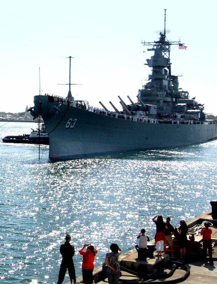 The USS Missouri floats in the harbor with onlookers n the docks