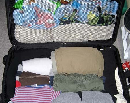 Suitcase of neatly-folded clothes and toiletries