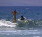 Surfer girl walking to the nose on Maui wave