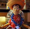 Toy Story character Woody sitting with lei and straw hat