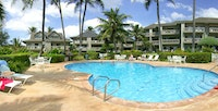 A bean-shaped pool surrounded by buildings at Castle Kaha Lani resort