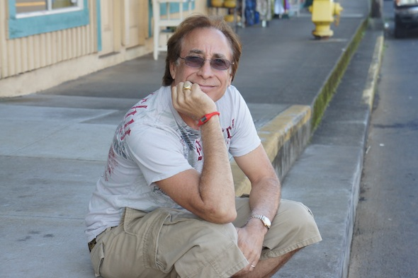 Bruce Fisher poses on a sidewalk