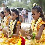 Hula girls wearing yellow floral dress and fresh lei while playing ipu