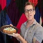 Owner of Otto Cakes holds a plate of fruit loop cheesecake