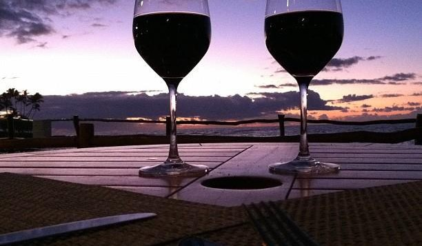 Two glasses of red wine with Hawaiian sunset in background