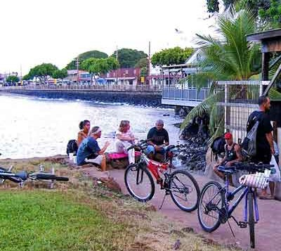 People hanging out on Lahaina Harbor seawall
