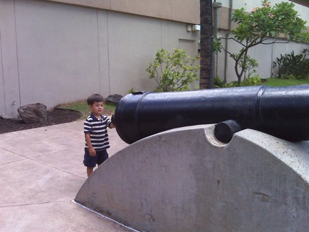 A small child touching a canon at Fort DeRussy