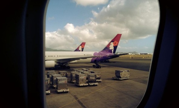 The tail of 2 Hawaiian Airlines jets from inside the window of another jet