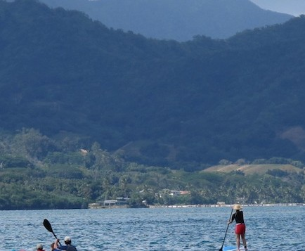 1 person stand-up paddling near a 2 person kayak