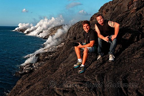 2men pose on a lava bluff near the water