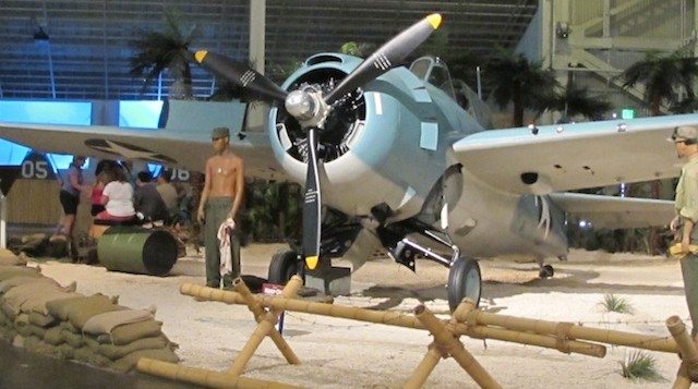 A scale model of a p-51 Mustang and girls hula dancing next to it