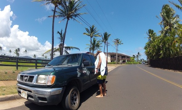 Man getting into a green truck on a hawaii street