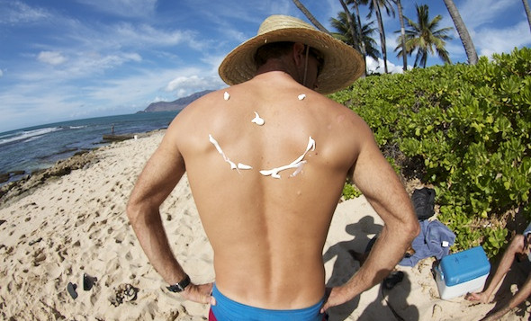 A man with sunscreen applied to his back in the shape of a smiley face