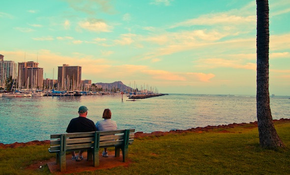 2 people sitting on a bench by the water