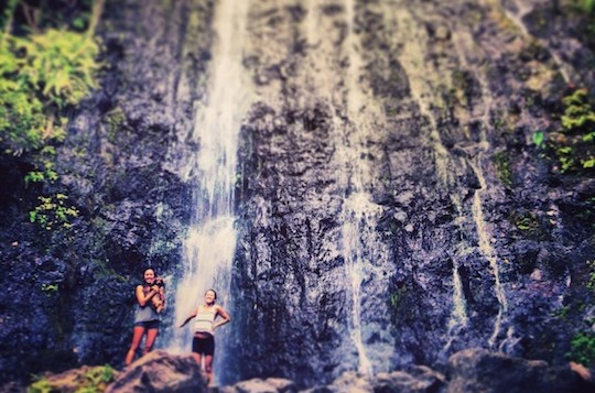 2 girls stand at the bottom of a huge waterfall
