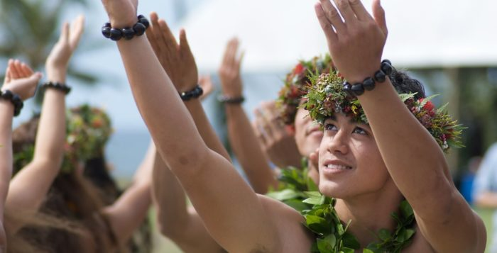 Young male Hula dancer wiht arms reaching up toward sky
