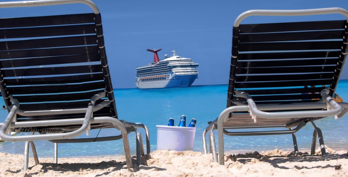 Chairs on the beach with ship in the distance