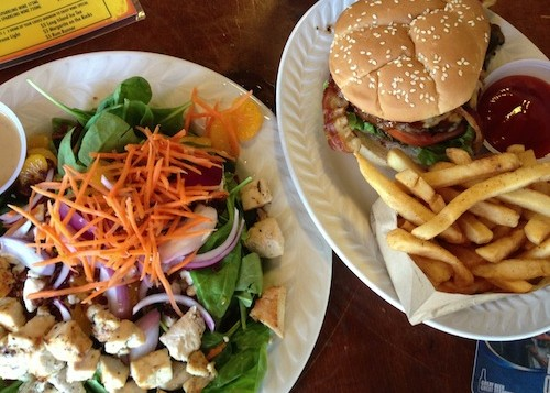 A burger with fries and a chicken salad