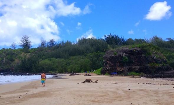 A man walks on the beach at Lawai Bay