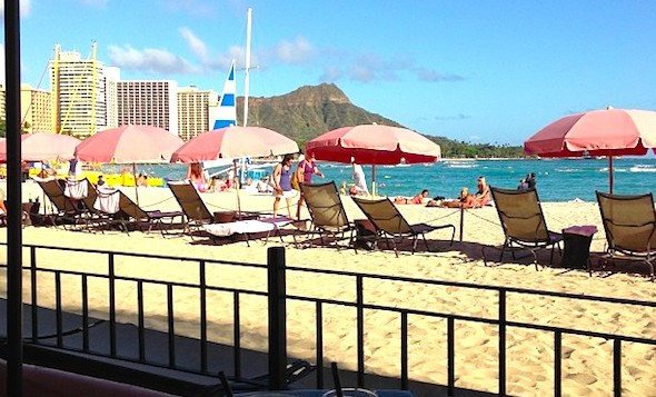 Several pink umbrellas on Waikiki Beach