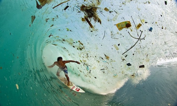 A surfer inside a pipe that is filled with garbage in Indonesia