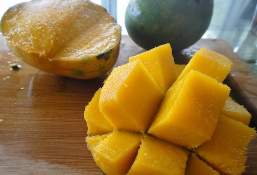 A mango that has been sliced int cubes with the skin on