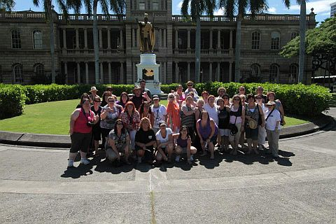 A group of Hawaii Five-0 fans pose in front of Iolani Palace