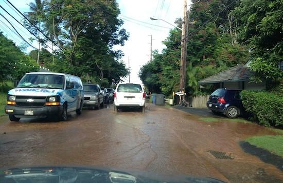 Brown water crosses the road as cars sit on Kamehameha highway