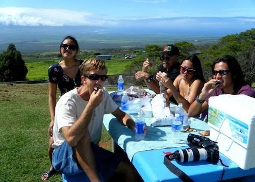 A group of people at a picnic table with Maui in the background