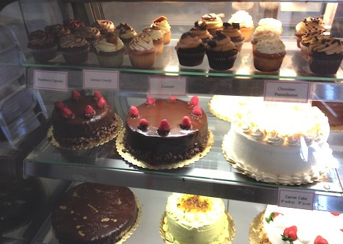 A storefront display of various cakes and pies at Cake Works