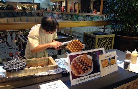 A woman makes bubble puffs at the Windward Mall farmers market