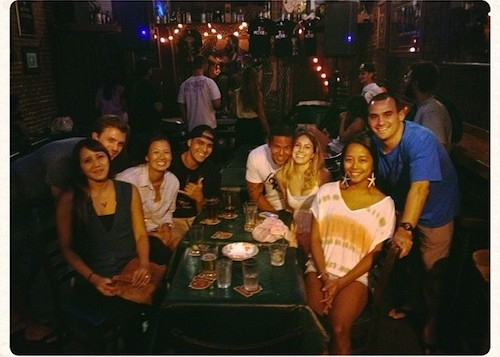People gathered around a table and smiling in a Honolulu pub called O'Tooles