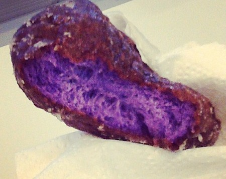 Half-eaten purple poi donut from Kamehameha Bakery