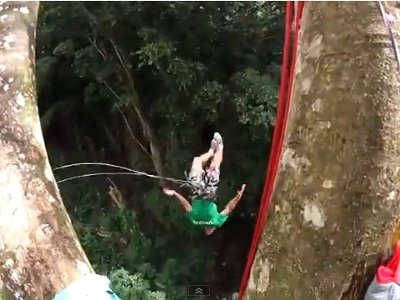 Man jumping off of a tree with a rope swing in Manoa